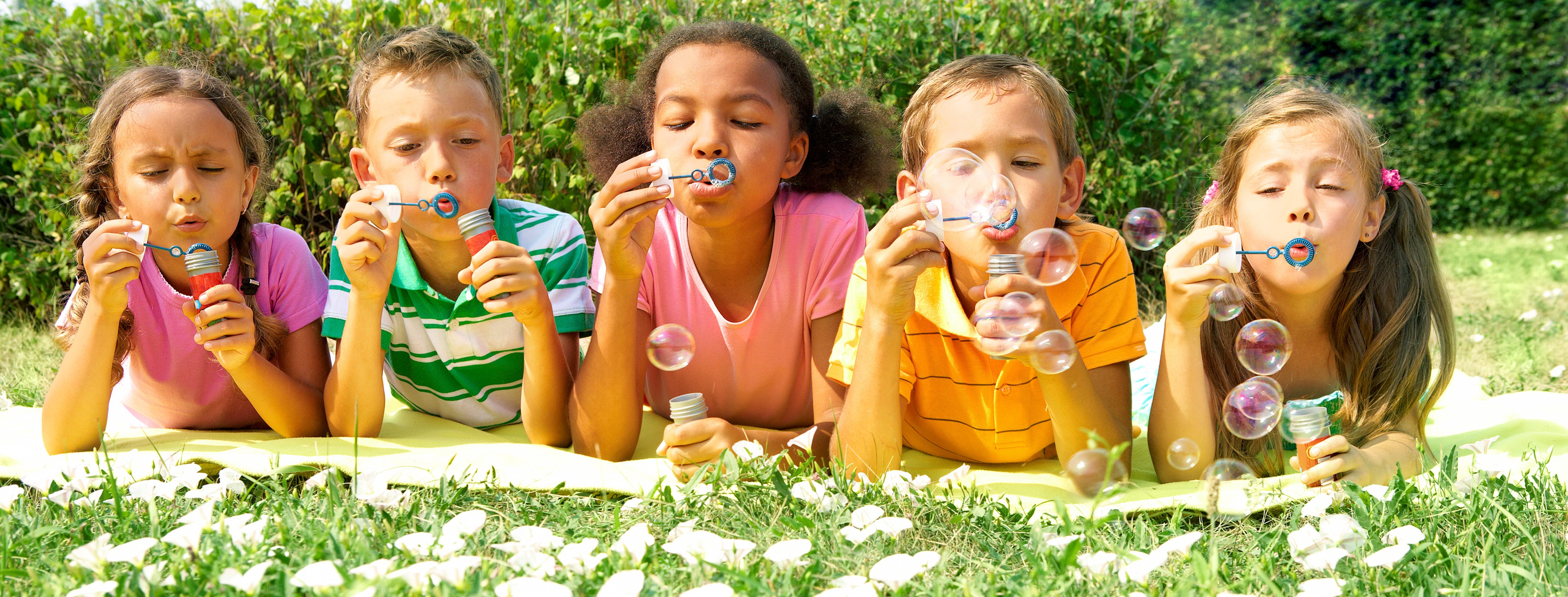 Kids blowing bubbles in grass